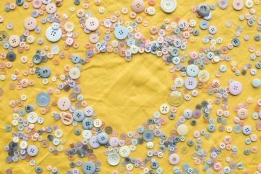 Top view of colorful buttons heart shaped frame on yellow cloth background with copy space stock vector