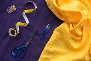 top view of scissors, measuring tape and box with pins over purple fabric