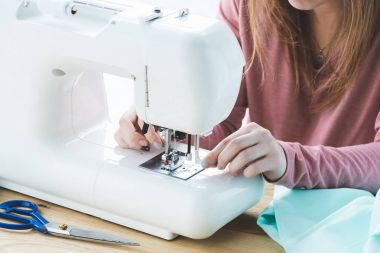cropped image of young seamstress using sewing machine at workplace