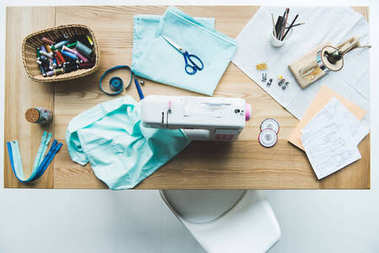 top view of seamstress workplace with fabric, sewing machine, drafts and stitchings