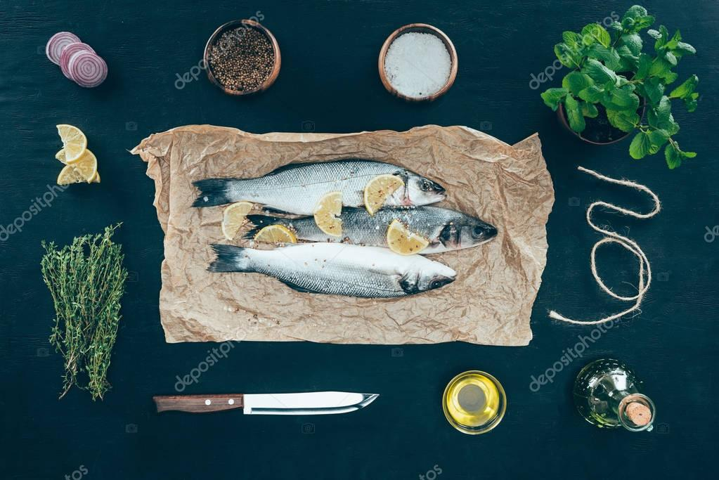 top view of gourmet fish with lemon slices on baking paper and spices on black