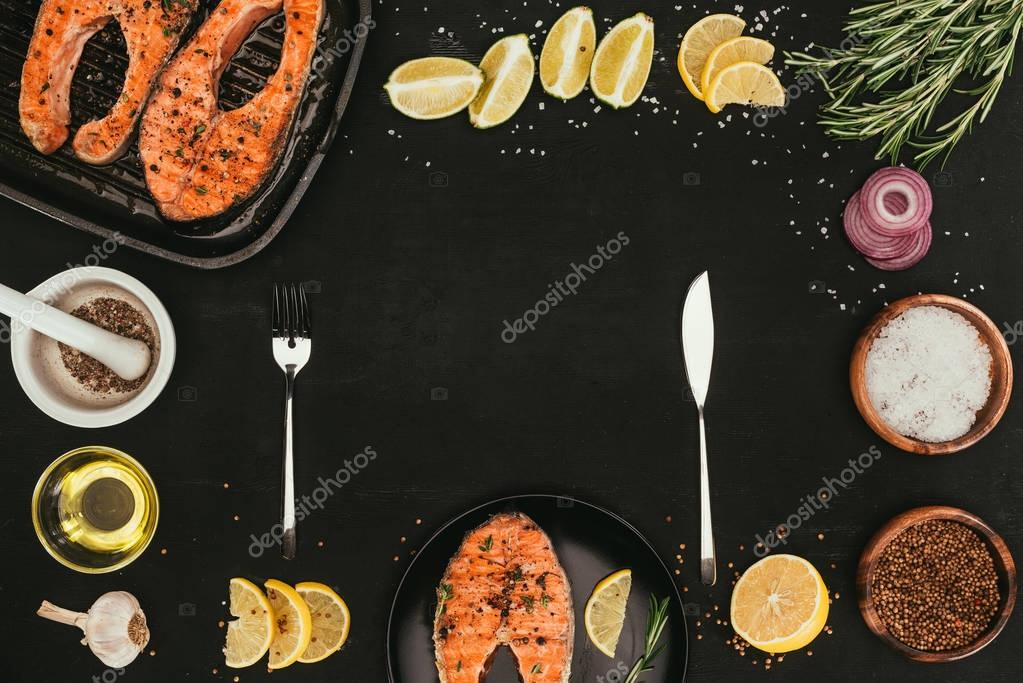 top view of grilled salmon steaks, cutlery and spices on black