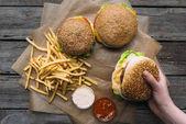 von Hand mit Hamburgern, Pommes und Soßen auf Backpapier auf Holztischplatte