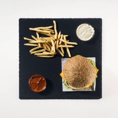 top view of hamburger, french fries and sauces on black stone board, isolated on white
