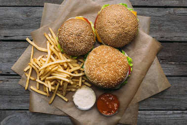top view of hamburgers, french fries, ketchup and mayonnaise on baking paper on wooden tabletop