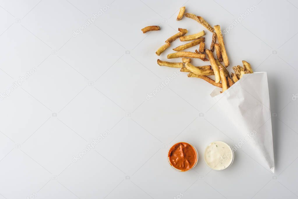top view of french fries in paper cone, mayonnaise and ketchup sauces, isolated on white