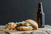 traditional homemade hamburger, french fries and bottle of beer on baking paper on wooden tabletop