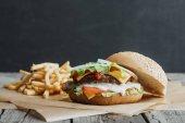 Fotografie tradiční domácí burger na pečícím papírem s hranolky