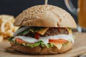 Nahaufnahme von weiblichen Händen mit traditionellen hausgemachten Hamburger auf Backpapier