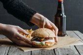 Fotografie oříznutý pohled ženských rukou s hamburger, hranolky a láhev piva na pečící papír na dřevěný stůl