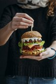 Fotografie oříznutý pohled ženy držící velké tradiční americký cheeseburger