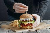 Fotografie oříznutý pohled ženské ruce velké chutné cheeseburger a hranolky na pečícím papírem