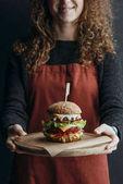 oříznutý pohled dívky v zástěra drží dřevěné desce s velkými domácí cheeseburger