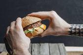 oříznutý pohled člověka drží chutné domácí cheeseburger