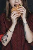 cropped view of tattooed girl biting tasty hamburger