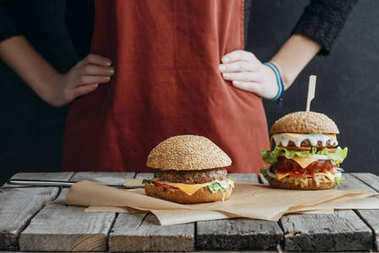 cropped view of girl in apron standing at wooden table with homemade cheeseburgers on baking paper