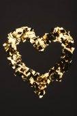 pohled shora zlaté konfety uspořádaných do tvaru srdce izolované na černém pozadí