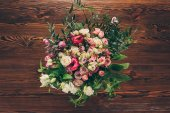 top view of bouquet of pink and white roses on wooden table