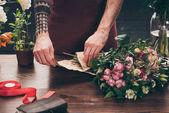 oříznutý obraz mužské květinářství s tetováním na ruce obtékání kytice v balení papíru