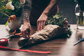cropped image of male florist wrapping bouquet in pack paper