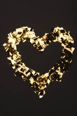 Top view of golden confetti arranged in heart shape isolated on black stock vector