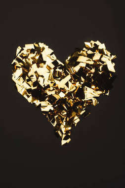 top view of golden confetti arranged in heart shape isolated on black