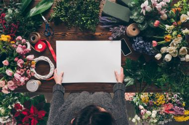 cropped image of florist holding empty sheet of paper in hands above working table