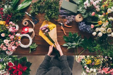 cropped image of florist wrapping bouquet in pack paper in shop