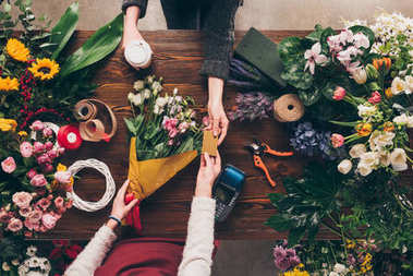 cropped image of customer giving florist credit card to pay for bouquet