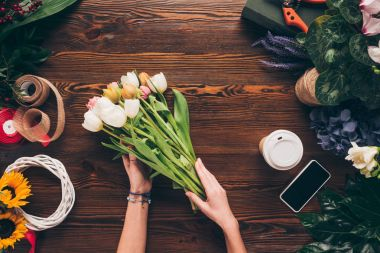 cropped image of florist making bouquet of tulips