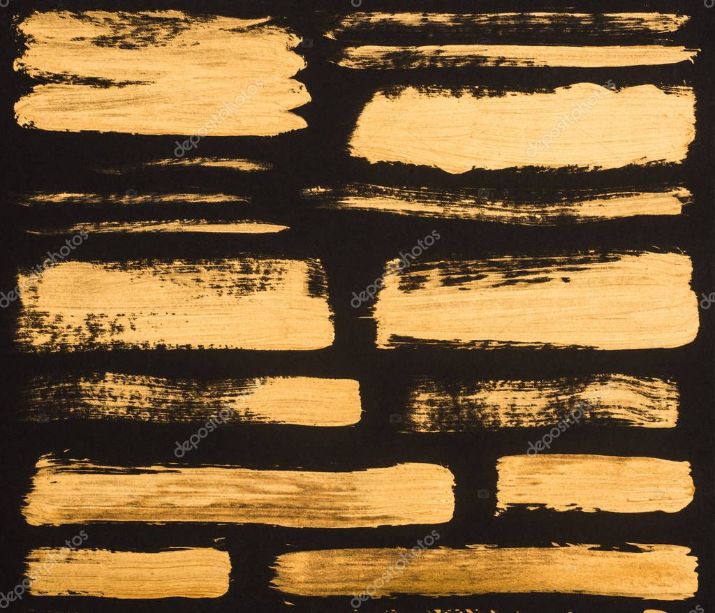close up view of golden paint strokes on black background