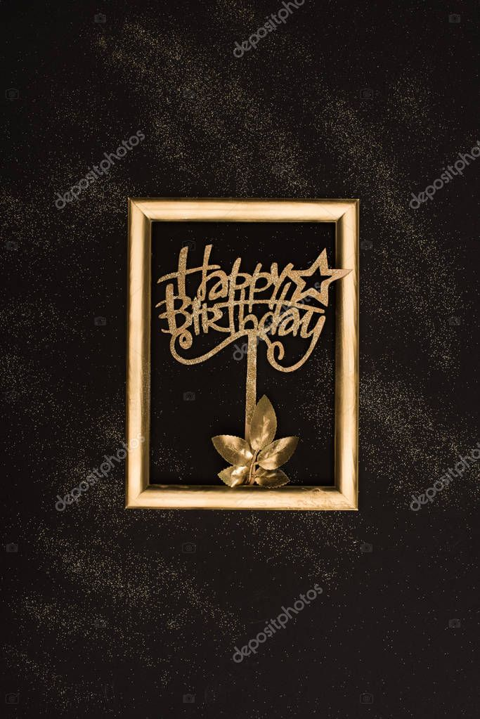 top view of golden happy birthday sign, plant and photo frame on black surface