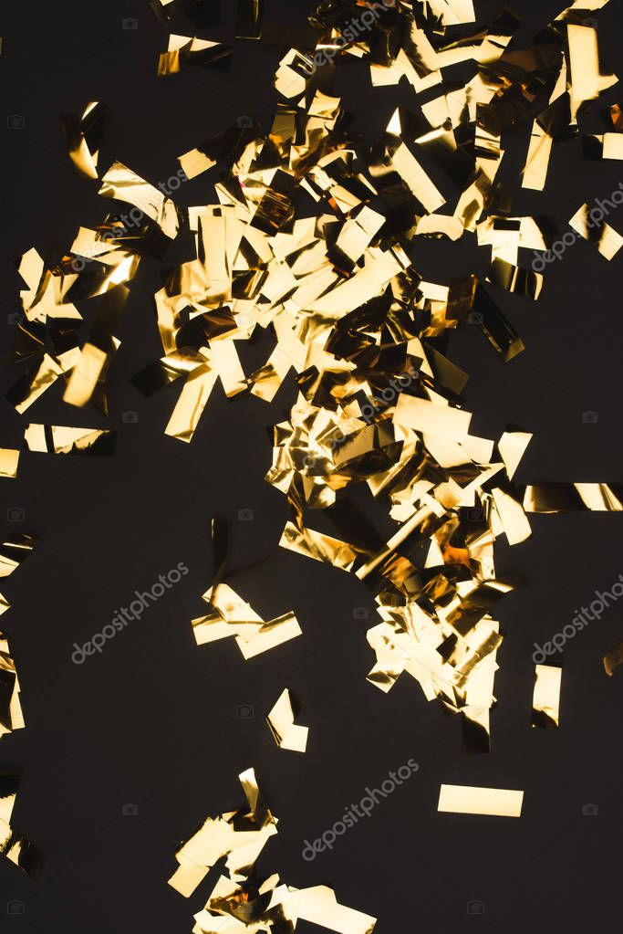 close up view of sparkling golden confetti isolated on black