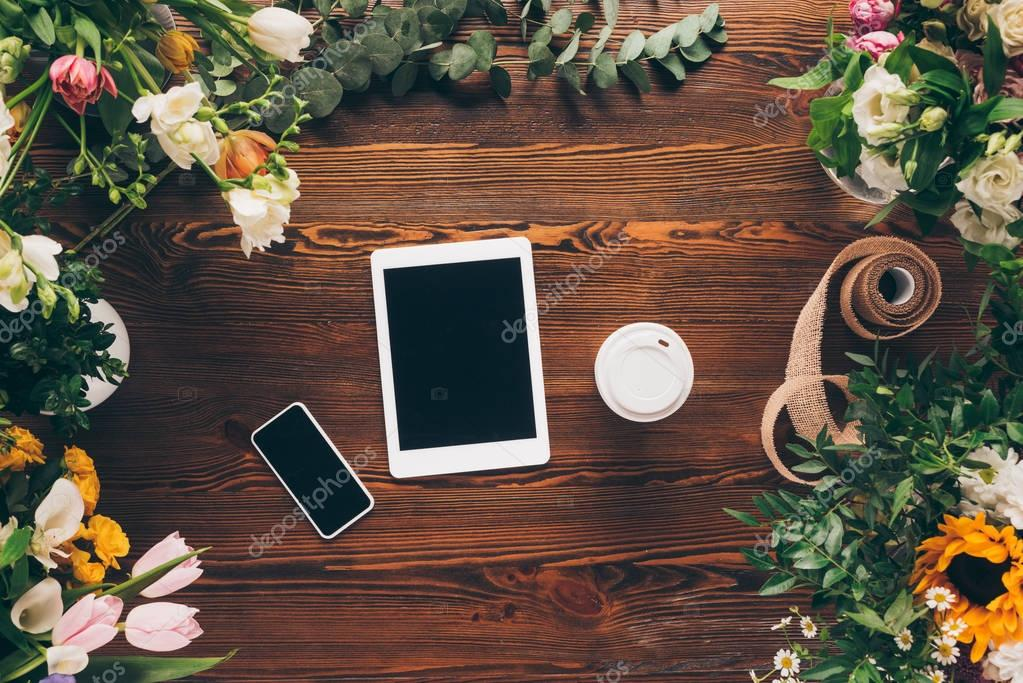 top view of digital devices and coffee in paper cup on wooden florist table