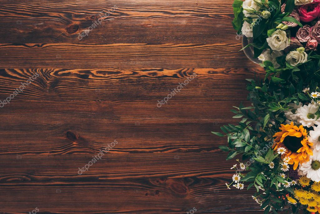 top view of different flowers on brown wooden table