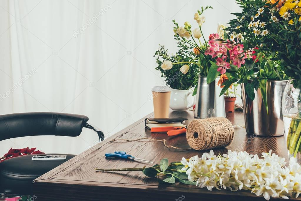 florist working table with flowers and tools