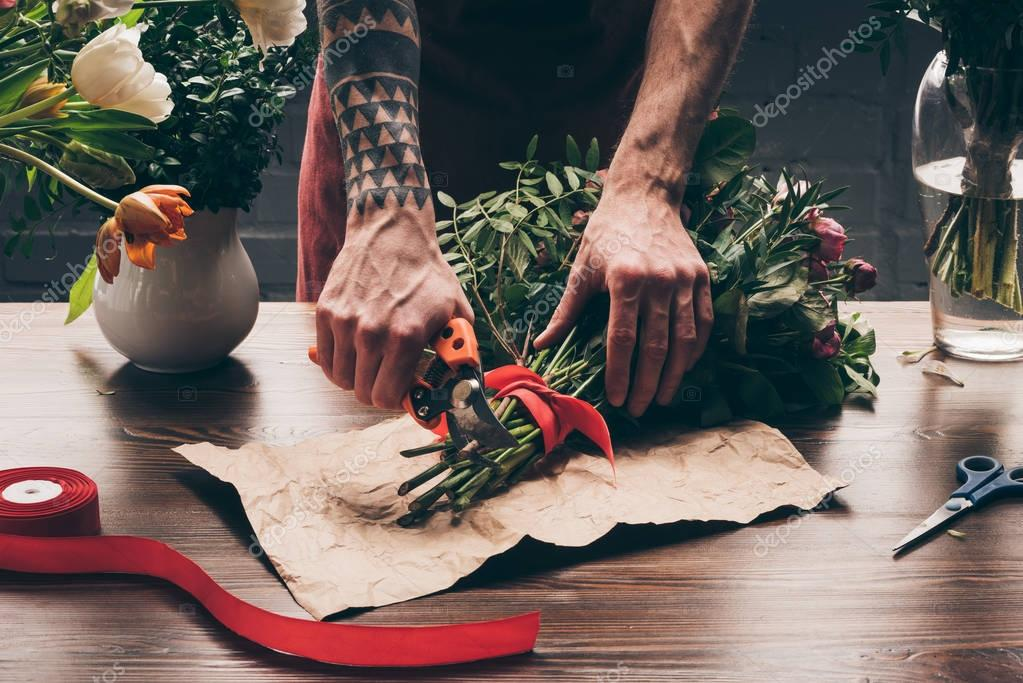 cropped image of florist with tattoo on hand cutting stalks with pruner