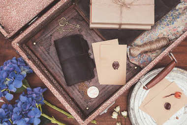top view of opened vintage suitcase with objects over wooden background