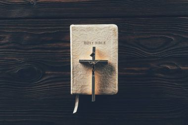 top view of christian cross on closed holy bible