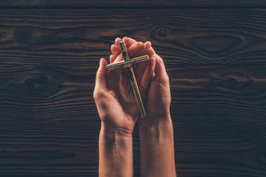 cropped image of woman holding cross in hands