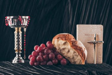 bread, grapes, bible, chalice and christian crosses on dark table for Holy Communion