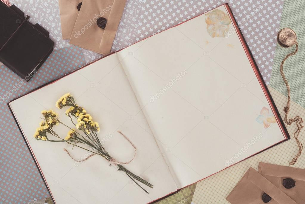 top view of opened book with flowers and copy space