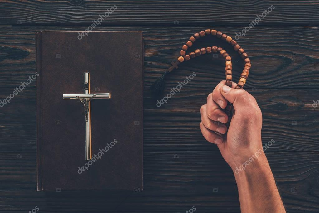 Cropped image of man holding rosary in hand stock vector