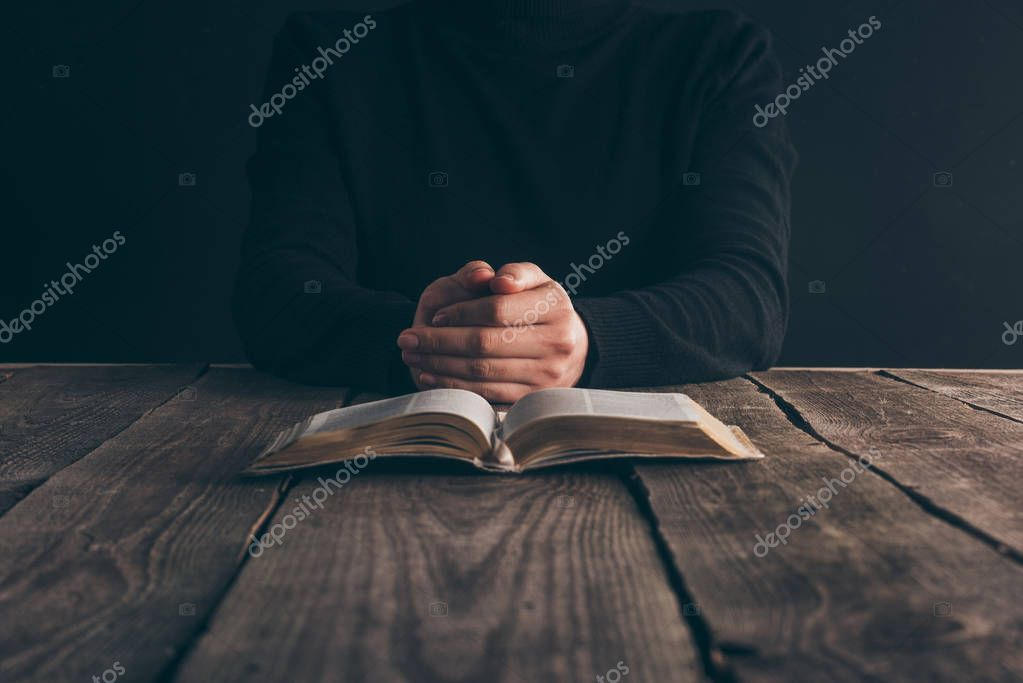 cropped image of nun sitting at table with bible and praying
