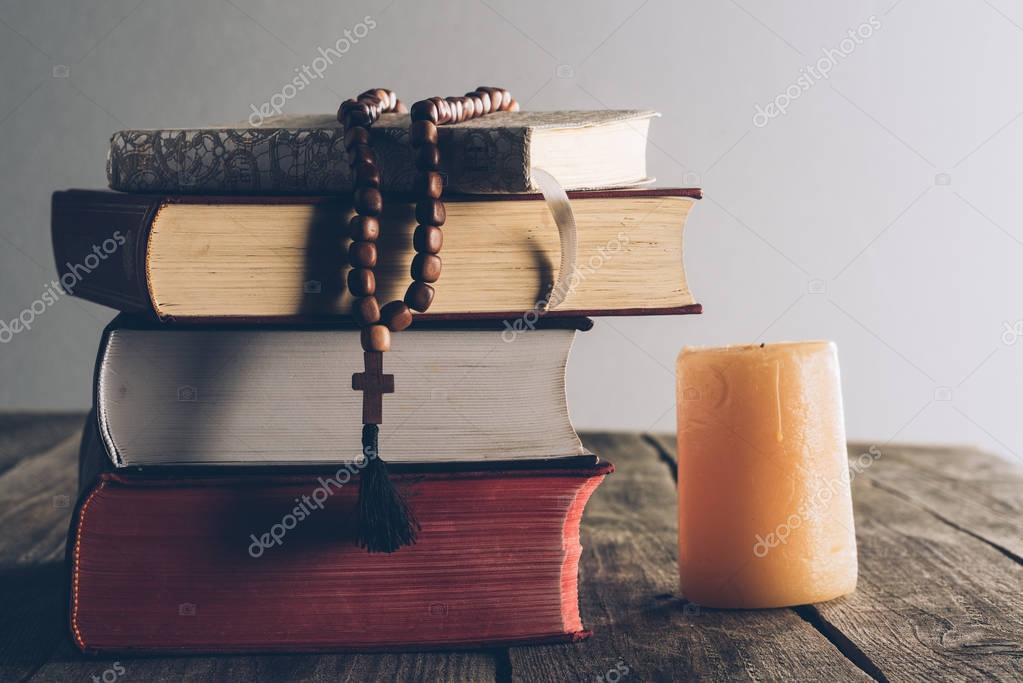 pile of religious books and christian cross on wooden table