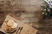 Fotografie top view of plate full of pancakes on wooden table with flowers bouquet