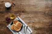 Fotografie top view of pancakes on striped napking and coffee cup on wooden table