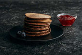 Photo stacked chocolate pancakes with blueberries and bowl of jam