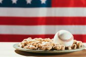 close-up view of baseball ball on plate with peanuts and american flag behind