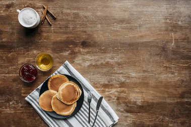 top view of pancakes on striped napking and coffee cup on wooden table